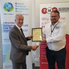 Terry Croft of NTDC presenting Geoff Howell of TMU with partner certificate